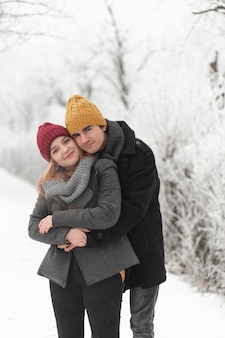Hombre abrazando a su novia al aire libre en la nieve.
