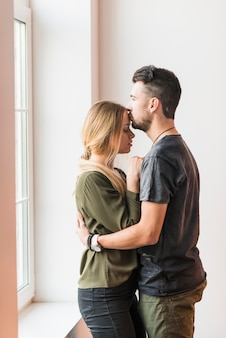 Hombre abrazando a su novia besándose en la frente en casa