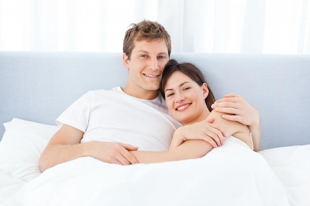 Hombre abrazando a su novia en su cama