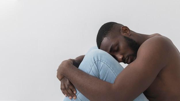 Hombre abrazándose a sí mismo y molesto