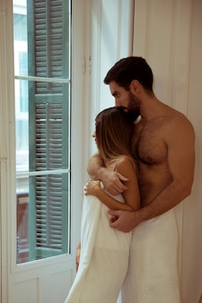 Hombre, abrazar, mujer, en, toallas, cerca, ventana