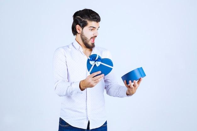Hombre abre una caja de regalo azul y se sorprende