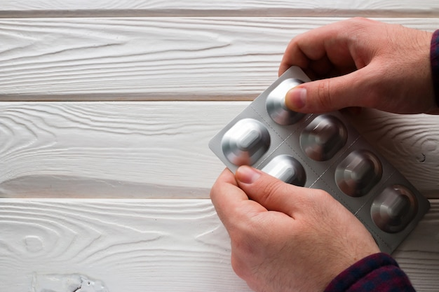 El hombre abre un paquete de tabletas de antibióticos en un blanco