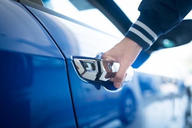 El hombre abre la puerta a un auto nuevo, la inspección del auto en la sala de exposición