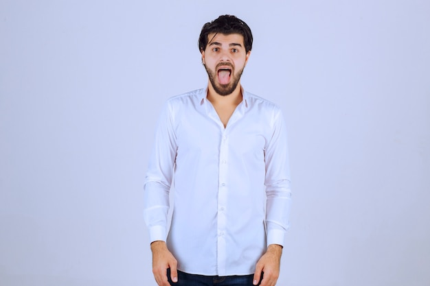 Hombre abriendo la boca porque tiene dolor de garganta.