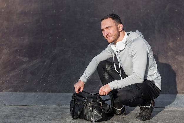 Hombre abriendo una bolsa de deporte y mirando a otro lado