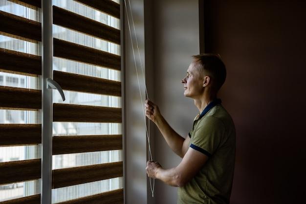 El hombre está abriendo las persianas.