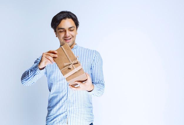Hombre abriendo su caja de regalo de cartón para comprobar el interior. foto de alta calidad
