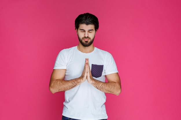 Hombre abriendo y uniendo sus manos para rezar por algo.