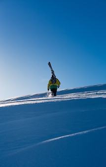 Hombre con un abrigo amarillo caminando en la nieve llevando una tabla de esquí