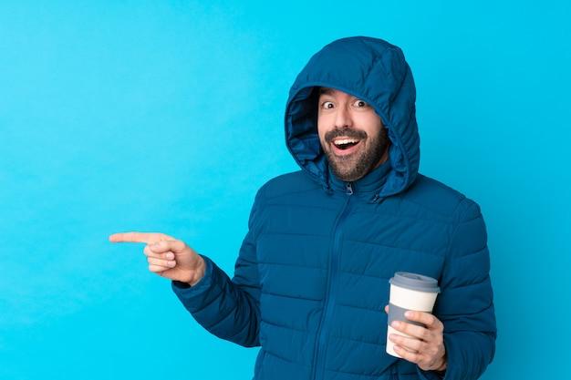 Hombre con abrigo de invierno sobre pared azul aislado