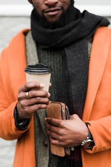 Hombre con abrigo naranja sosteniendo una taza de café