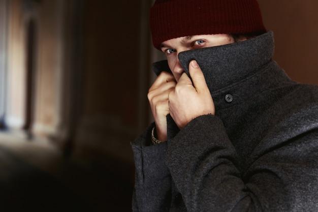 El hombre con un abrigo oculta su rostro detrás del cuello alto