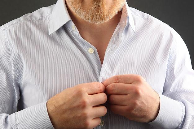El hombre abrocha los botones de su camisa