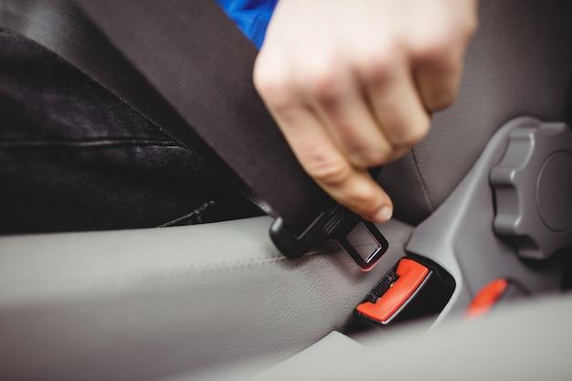Hombre abrochándose el cinturón de seguridad en una camioneta