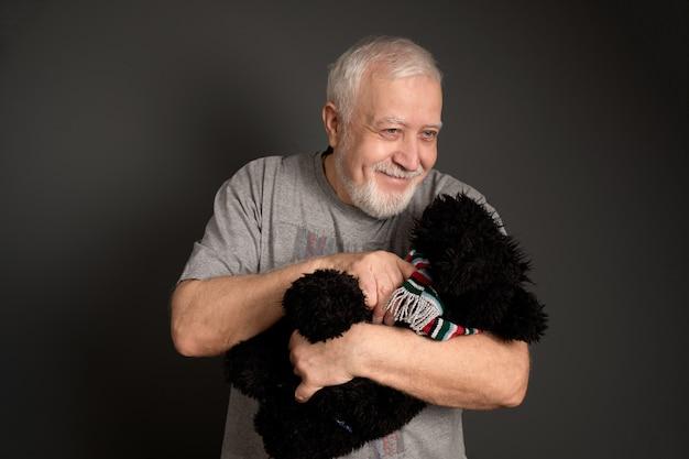 Un hombre-abuelo de pelo canoso, sonriente y amable, con un osito de peluche.