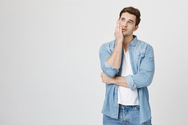 Hombre aburrido y cansado mirando hacia arriba, facepalm sobre pared blanca
