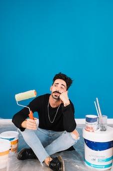 Hombre aburrido con materiales de pintura