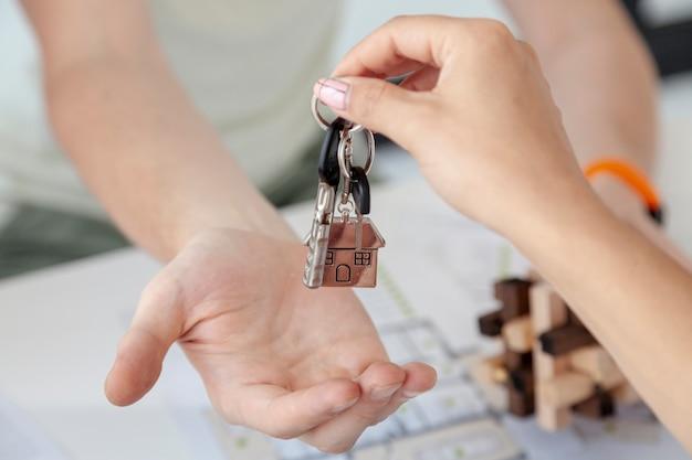Hombre aceptando las llaves para un primer plano de casa nueva