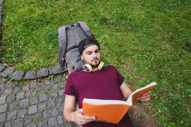 Hombre acostado en el banco en la lectura del parque
