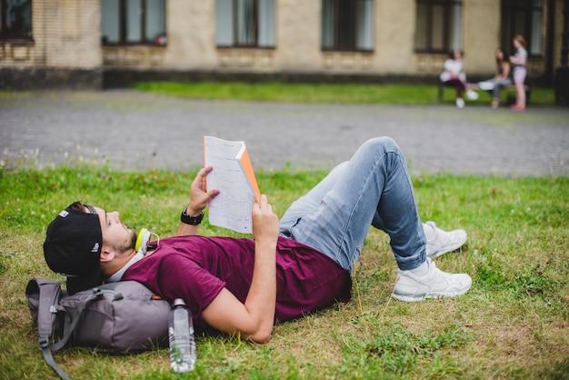 Hombre, acostado, pasto, lectura
