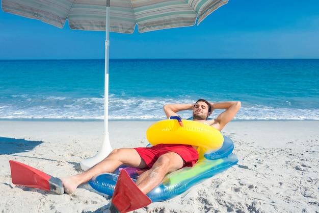 Hombre acostado en la playa con aletas y anillo de goma