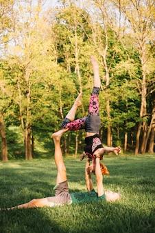 Hombre acostado sobre el césped y el equilibrio de la mujer en la mano y la pierna en el parque