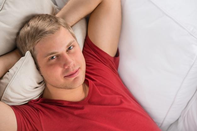 Hombre acostado en el sofá y relajante