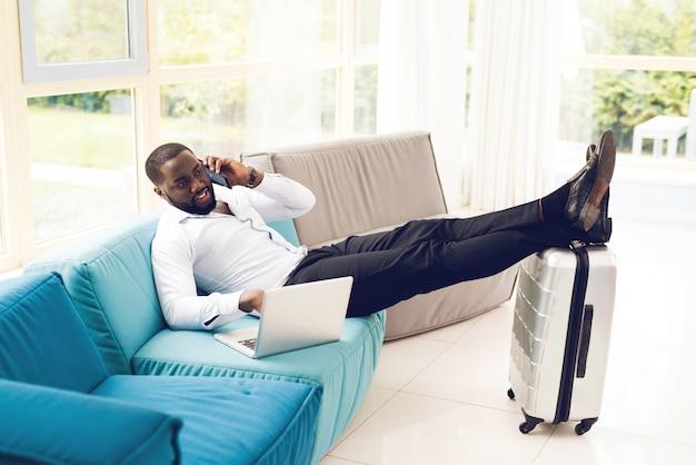 El hombre está acostado en el sofá en la sala de espera en el aeropuerto