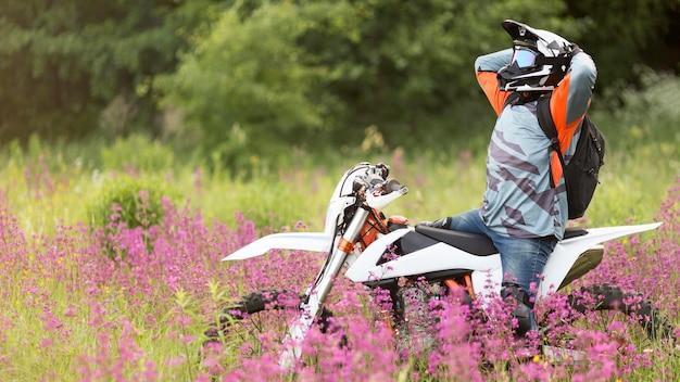 Hombre activo feliz de andar en moto en la naturaleza
