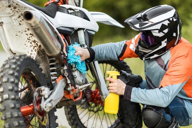 Hombre activo limpiando moto al aire libre