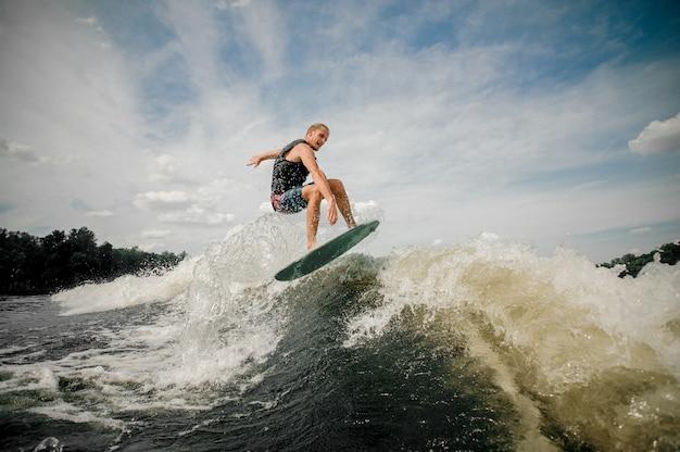 Hombre activo saltando sobre las olas del río