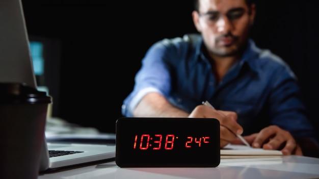 Hombre adicto al trabajo que trabaja horas extras por la noche en la oficina