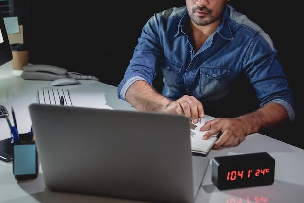 Hombre adicto al trabajo trabajando en una computadora portátil hasta tarde en la noche en la oficina