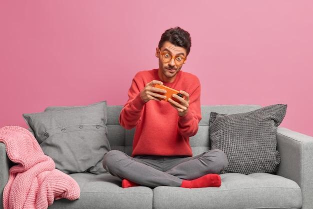 Hombre adicto juega juegos en línea en el teléfono inteligente se sienta con las piernas cruzadas en el cómodo sofá