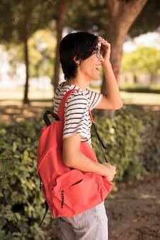 Hombre adolescente asiático con mochila riendo