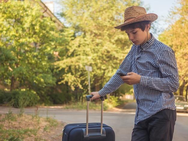 Hombre adolescente joven en el arrastre casual en la calle de la ciudad con equipaje y que usa el teléfono