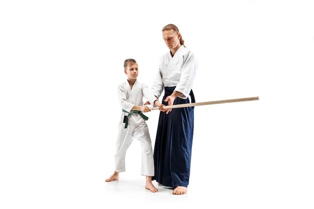 Hombre y adolescente luchando con espada de madera en el entrenamiento de aikido en la escuela de artes marciales