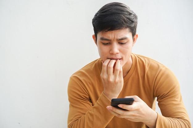Hombre adolescente muerde un dedo mientras lee un comentario en las redes sociales