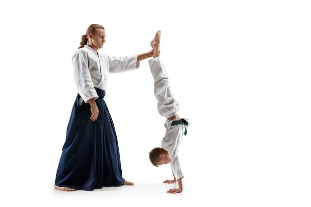 Hombre y adolescente peleando en el entrenamiento de aikido en la escuela de artes marciales. concepto de deporte y estilo de vida saludable. fightrers en kimono blanco sobre fondo blanco. hombres de karate con caras concentradas en uniforme.