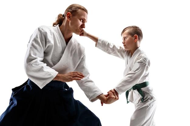 Hombre y adolescente peleando en el entrenamiento de aikido en la escuela de artes marciales. concepto de deporte y estilo de vida saludable. fightrers en kimono blanco sobre pared blanca