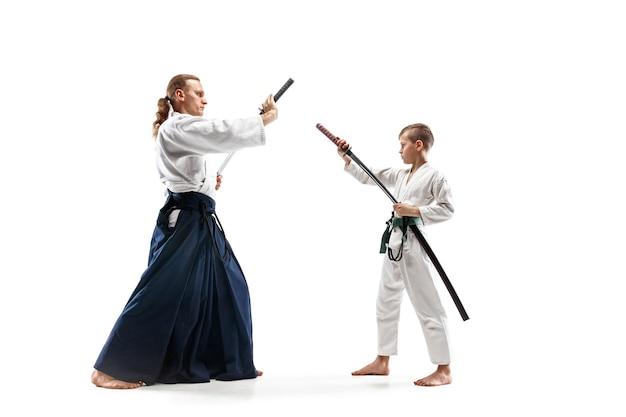 Hombre y adolescente peleando en el entrenamiento de aikido en la escuela de artes marciales