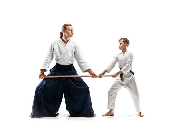 Hombre y adolescente peleando con espada de madera en el entrenamiento de aikido en la escuela de artes marciales. concepto de deporte y estilo de vida saludable. fightrers en kimono blanco sobre fondo blanco. hombres de karate en uniforme.