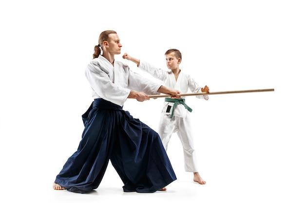 Hombre y adolescente peleando con espada de madera en el entrenamiento de aikido en la escuela de artes marciales.