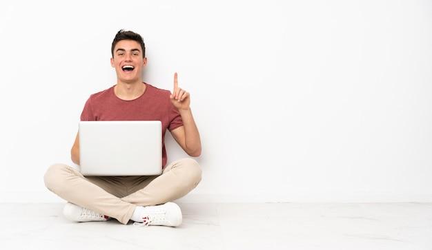 Hombre adolescente sentado en la flor con su computadora portátil pensando en una idea apuntando el dedo hacia arriba