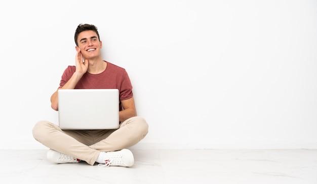 Hombre adolescente sentado en la flor con su computadora portátil pensando en una idea