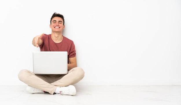 Hombre adolescente sentado en el suelo con su computadora portátil dándose la mano por cerrar un buen negocio