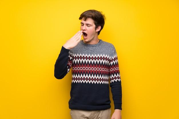 Hombre adolescente sobre una pared amarilla bostezando y cubriendo la boca abierta con la mano