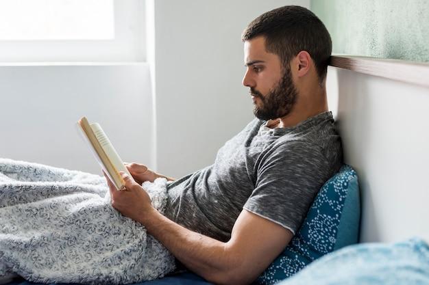 Hombre adulto acostado en la cama y leyendo