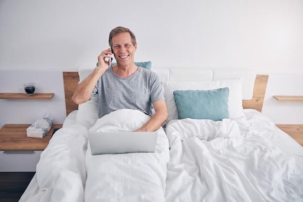 Hombre adulto alegre feliz que tiene una conversación agradable mientras trabaja desde el autoaislamiento, manteniendo la computadora portátil de rodillas
